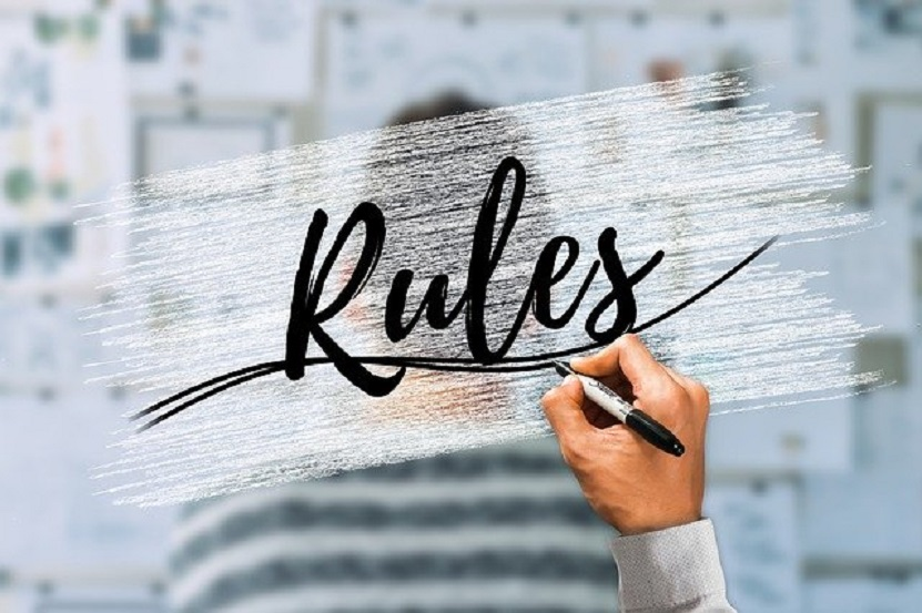 hand writing the word rules with black pen